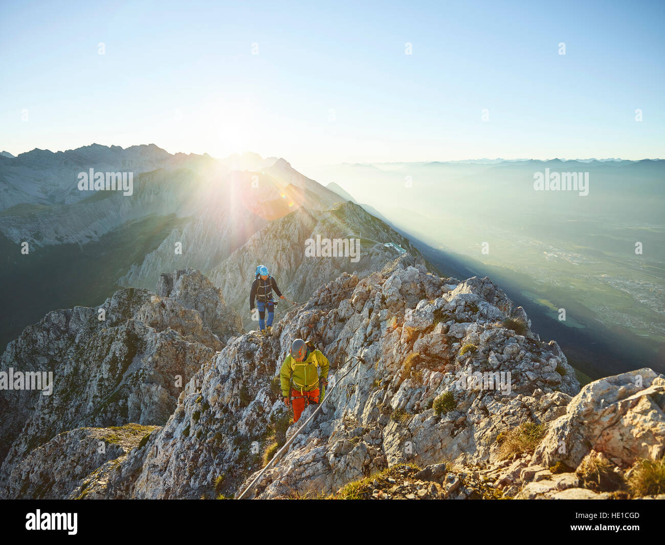 Sunrise on ridge, via ferrata, two climbers attached to steel cable, Nordkette Innsbruck, Tyrol, Austria - Stock Image