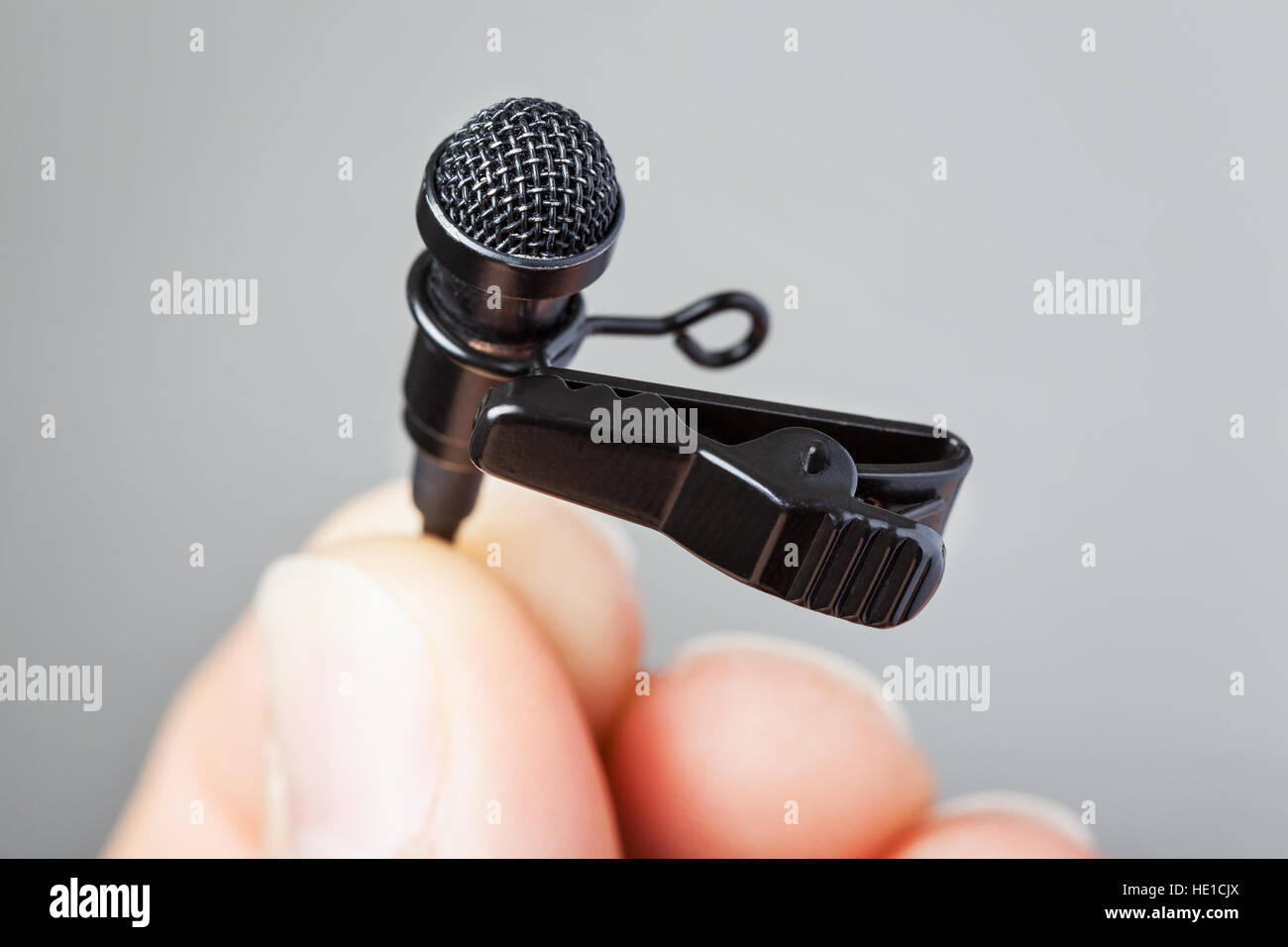 Close-up of a hand holding a tie-clip microphone with a plain background - Stock Image