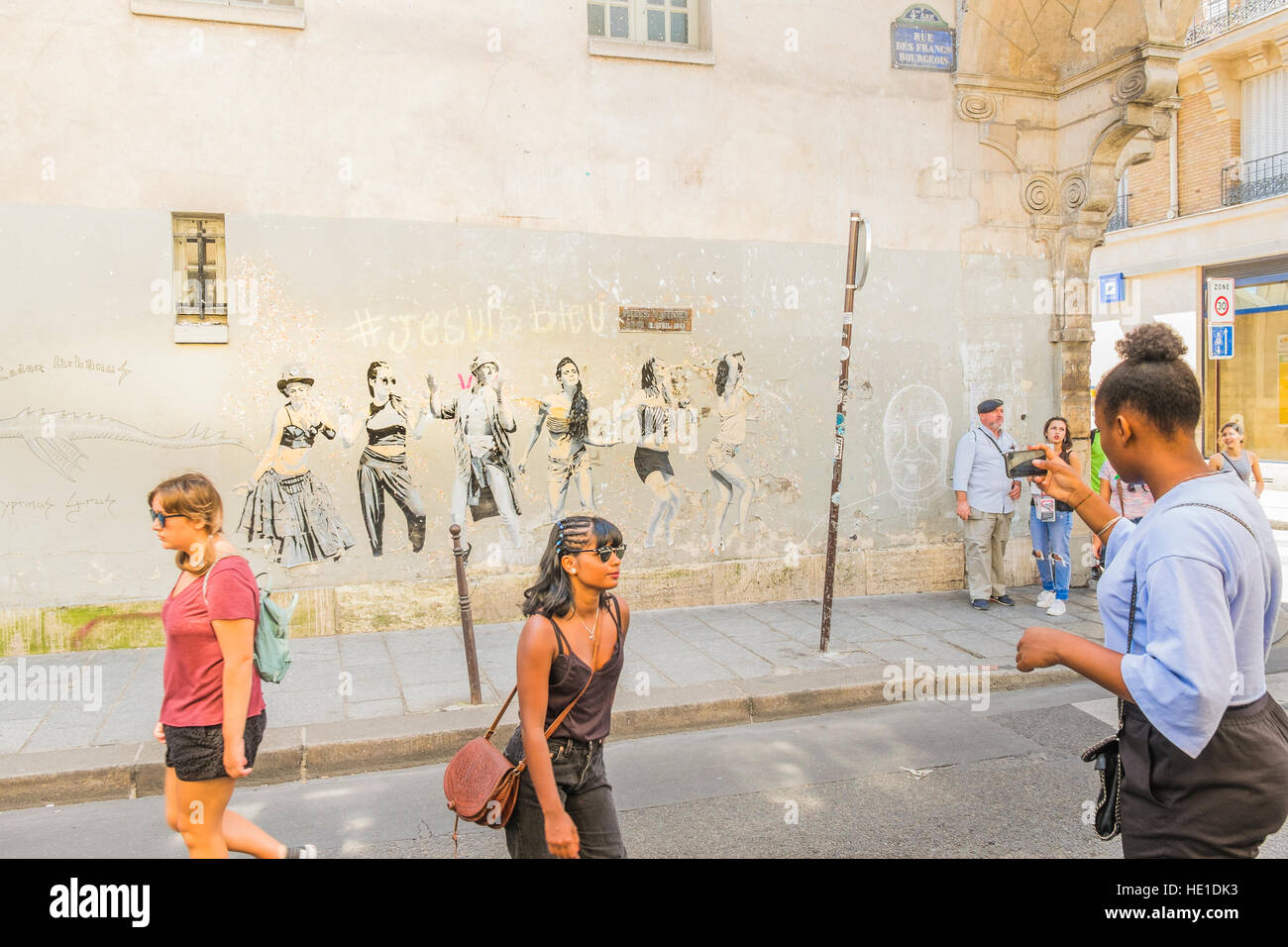 street scene in front of graffito showing dancing young people - Stock Image
