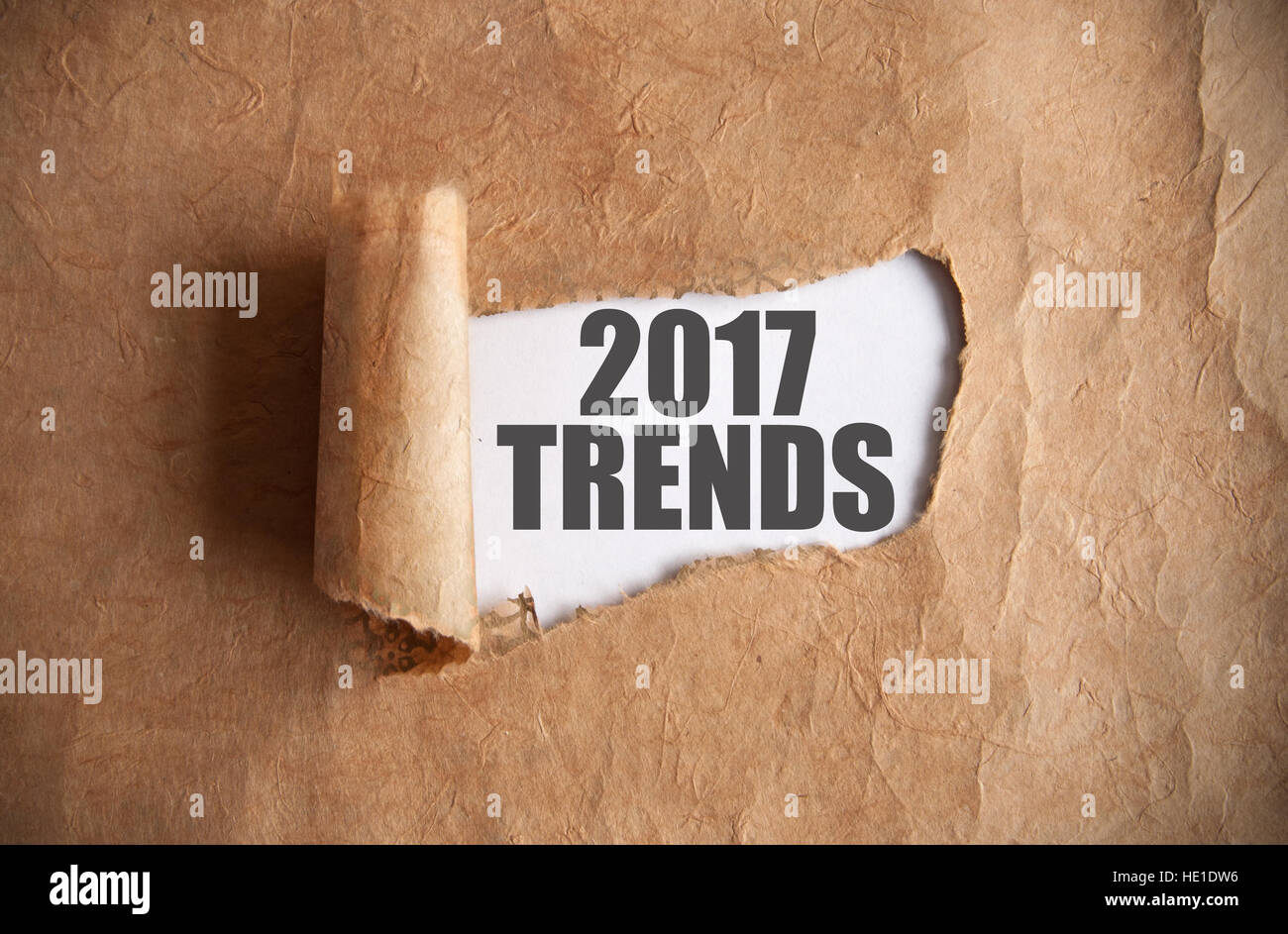 Torn piece of scroll uncovering 2017 trends underneath - Stock Image