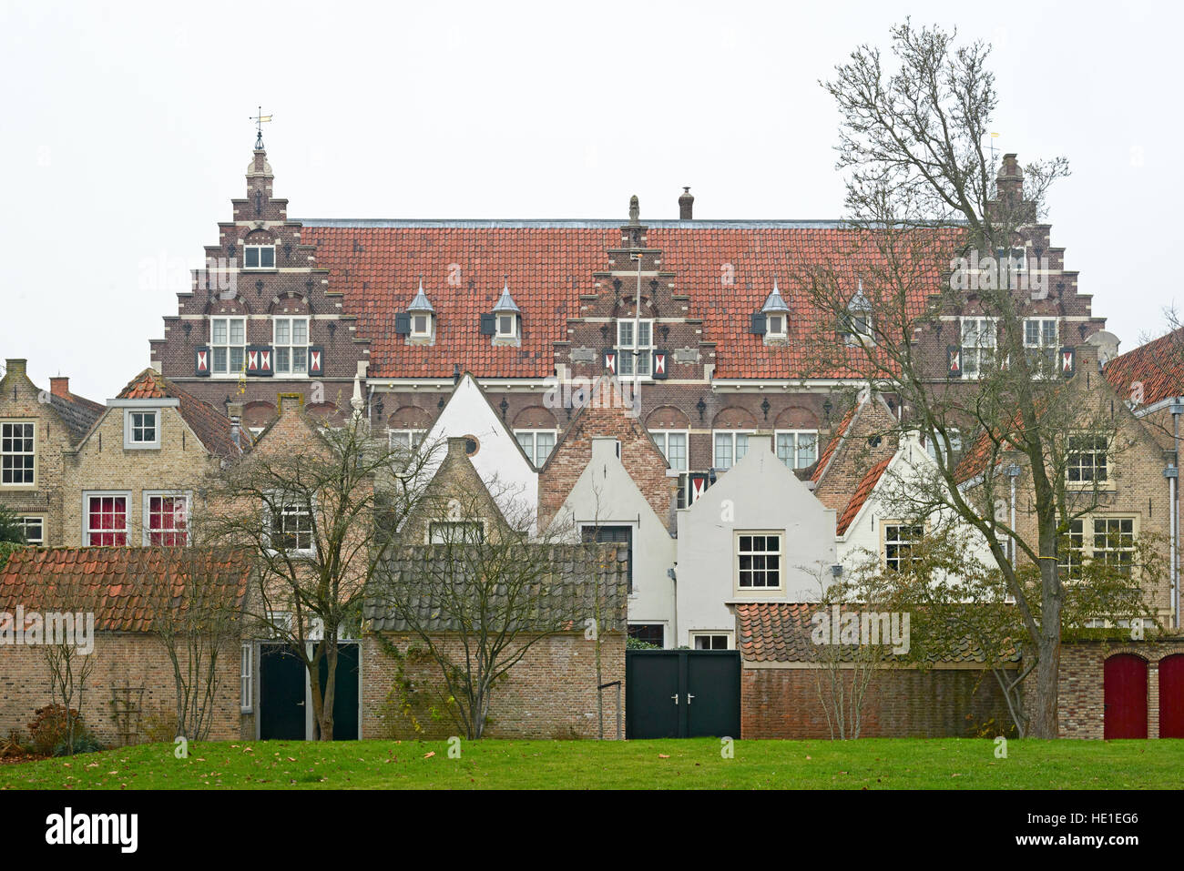 View on the Statenschool in Dordrecht with 17th century houses in front; built in 1913 in the neo-dutch Renaissance - Stock Image