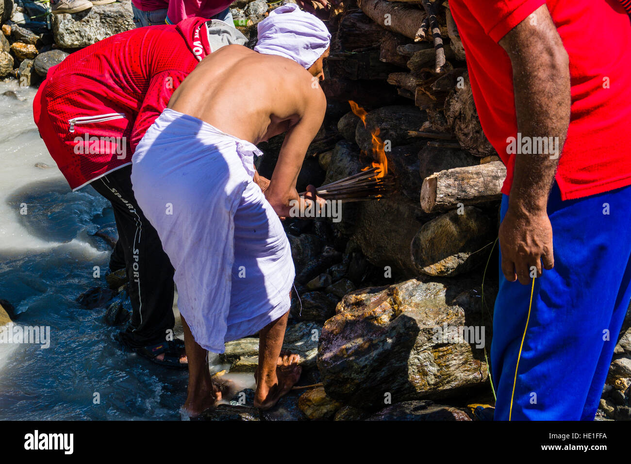 A man is lightning the fire at the funeral of a death body at the cremation ground on the bank of the river Kali - Stock Image