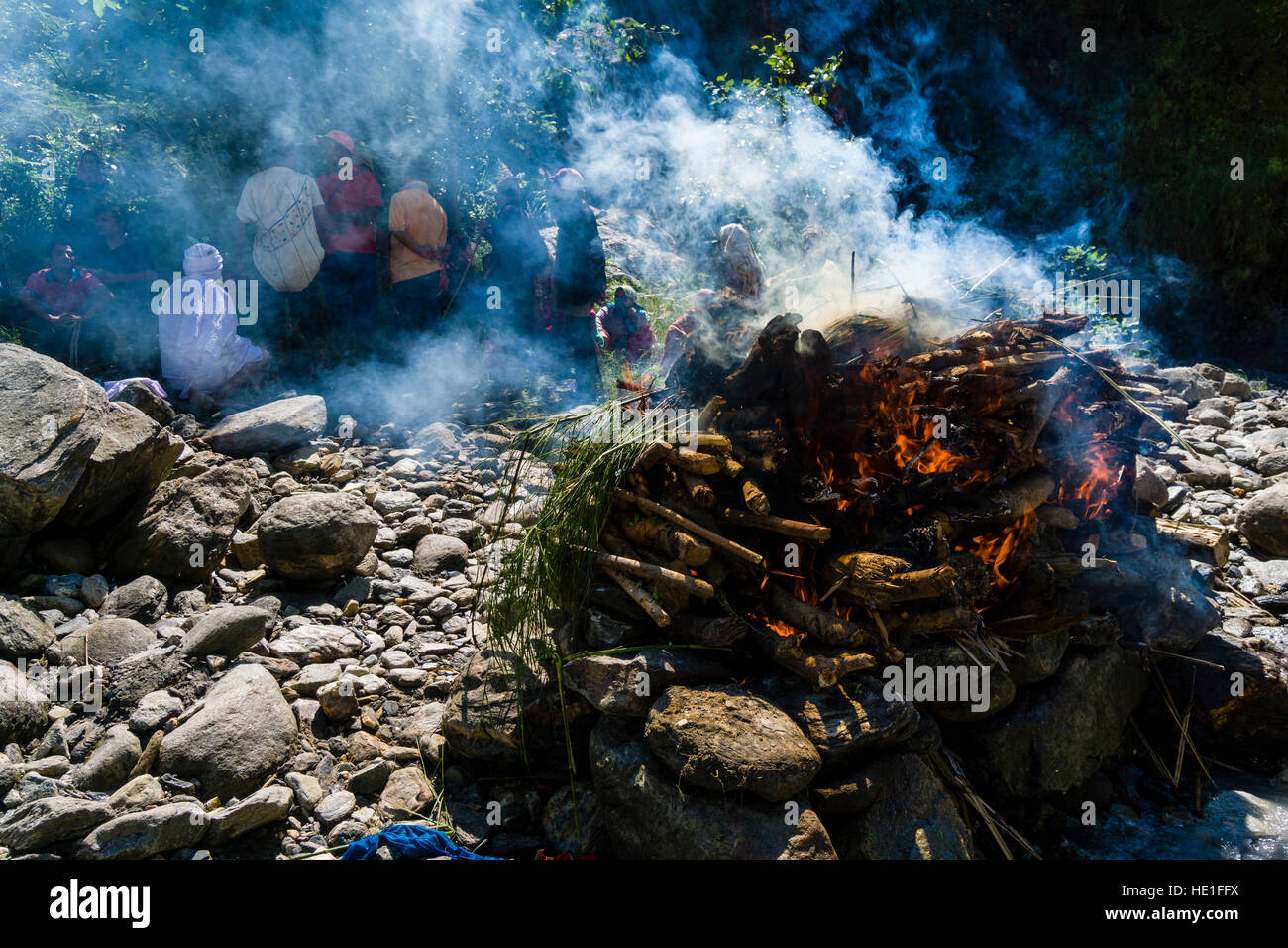 The fire of the funeral of a death body at the cremation ground on the bank of the river Kali Gandaki is producing - Stock Image