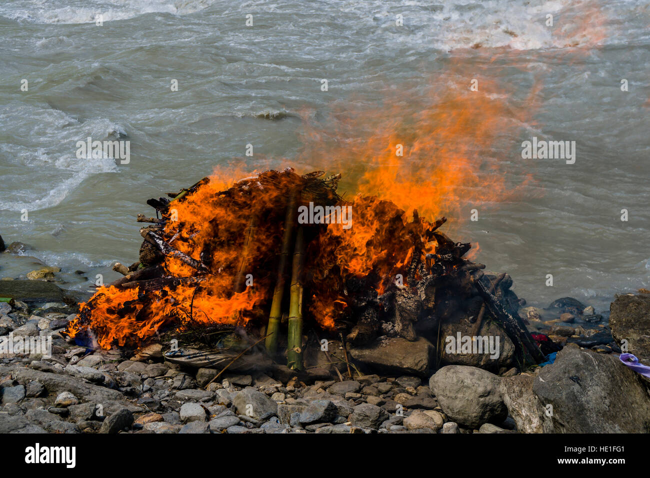 The fire of the funeral of a death body at the cremation ground on the bank of the river Kali Gandaki is burning Stock Photo