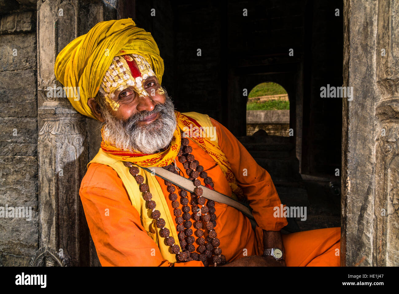 Portait of a Sadhu, holy man, sitting at a little shrine at Pashupatinath temple at the banks of Bagmati River - Stock Image