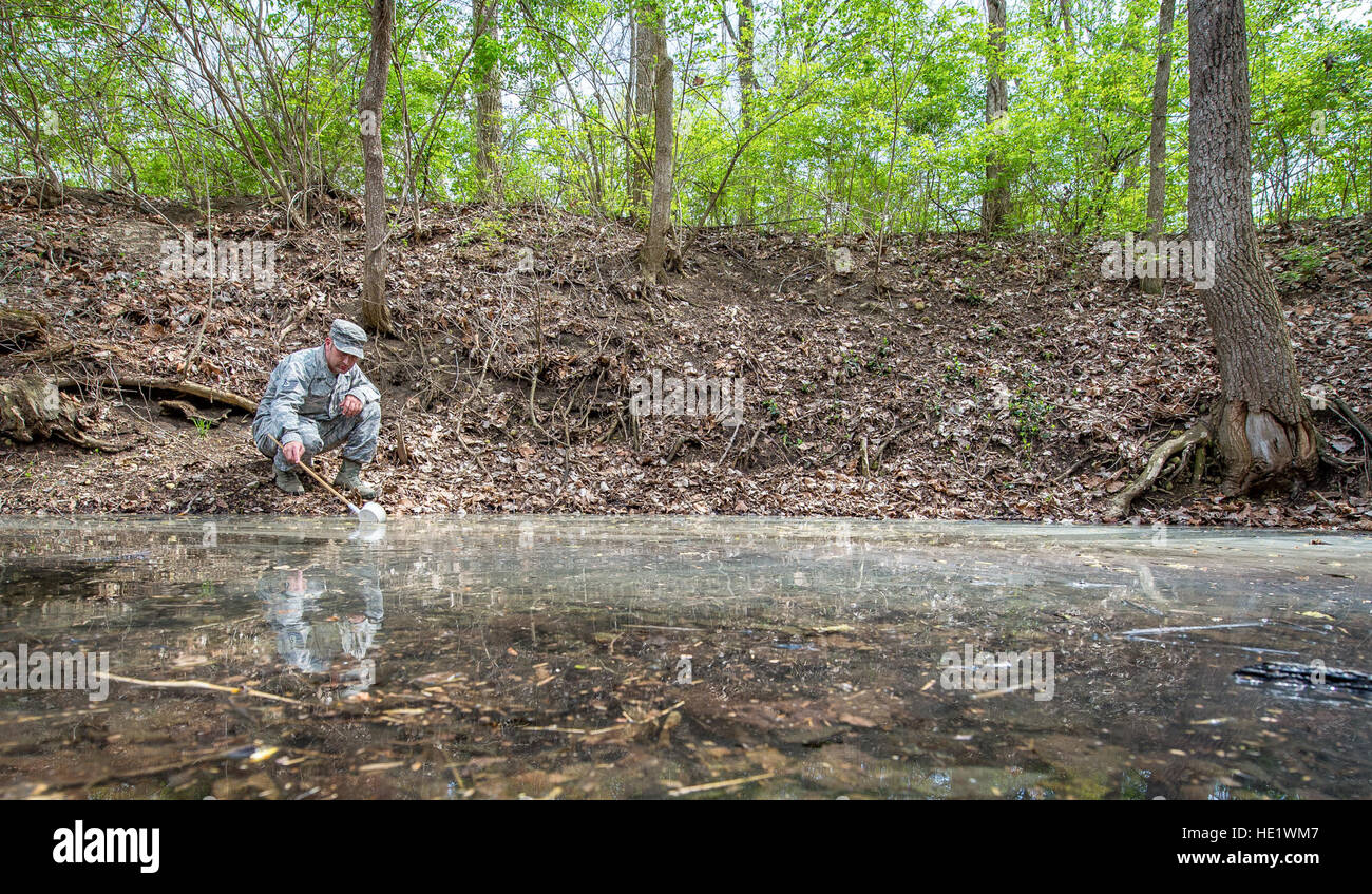 Tech. Sgt. Jonathan Eckley skims a creek-bed to look for mosquitos at Wright-Patterson Air Force Base, Ohio on April Stock Photo