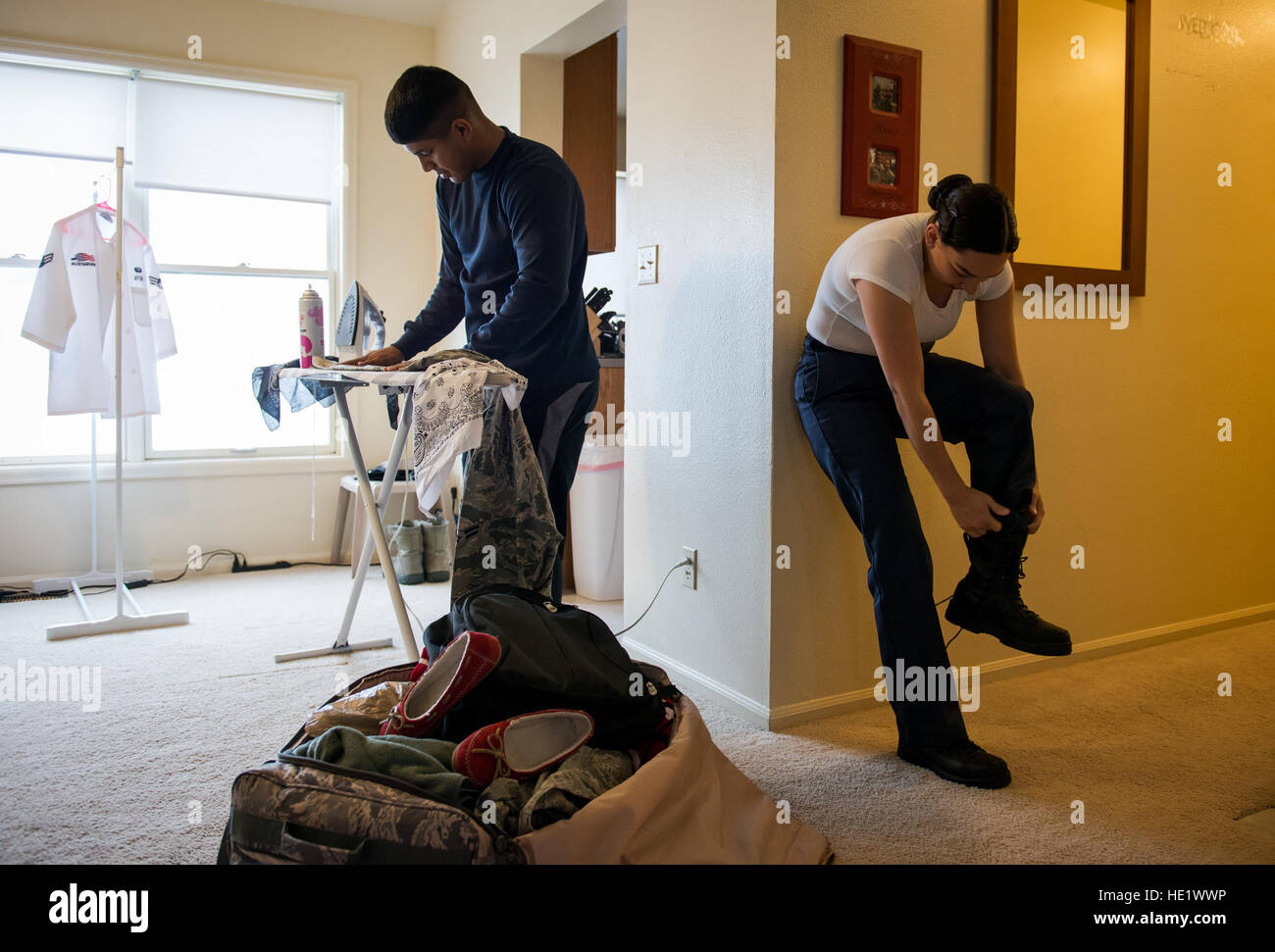 Airman 1st Class Ozzie Galvan left helps his wife, Airman 1st Class Alexandra Ayub, prepare for a four-day deployment - Stock Image