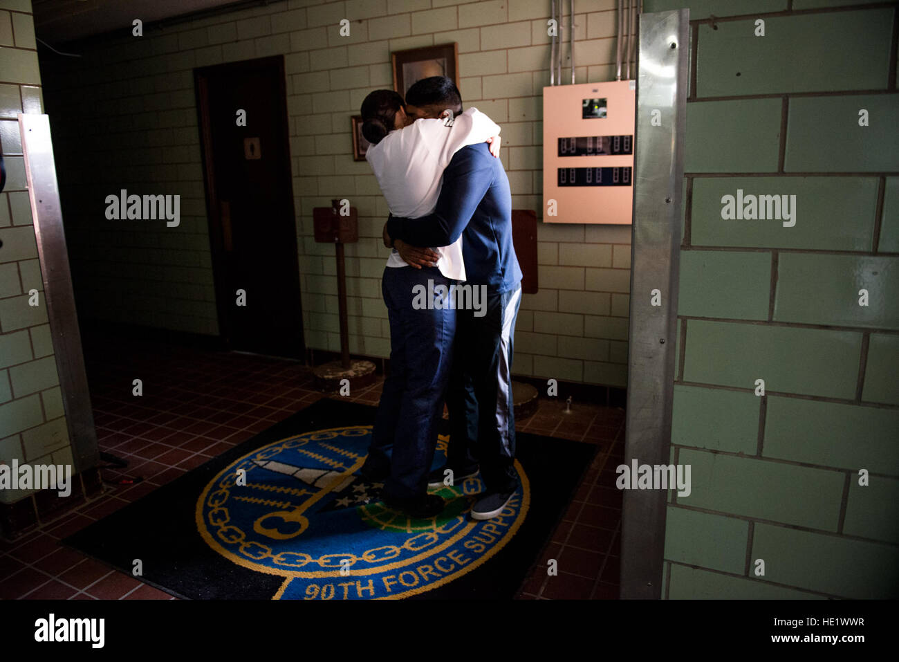 Airman 1st Class Alexandra Ayub, a missile chef, hugs her husband, Airman 1st Class Ozzie Galvan, before leaving - Stock Image