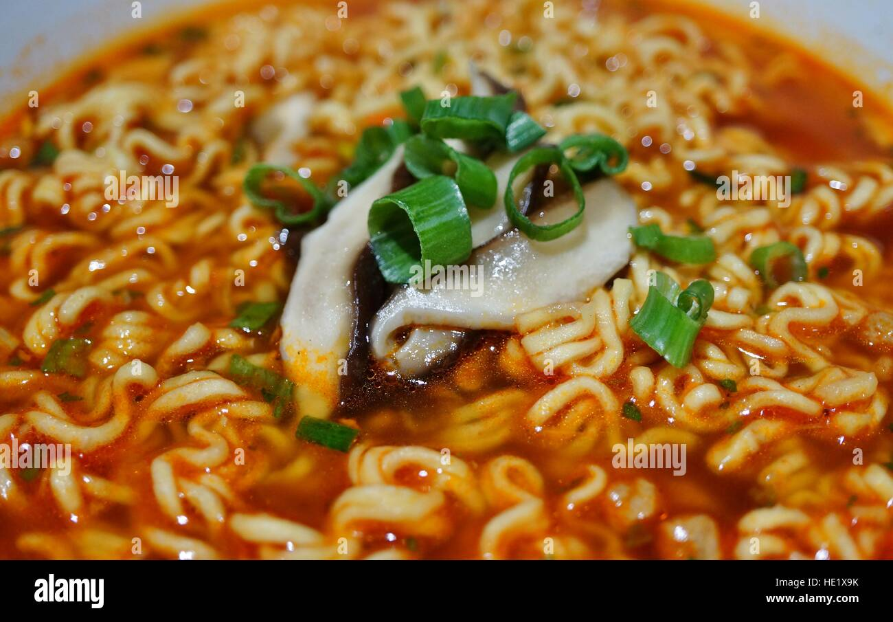 Bowl of spicy ramen noodle soup with scallions and mushrooms - Stock Image
