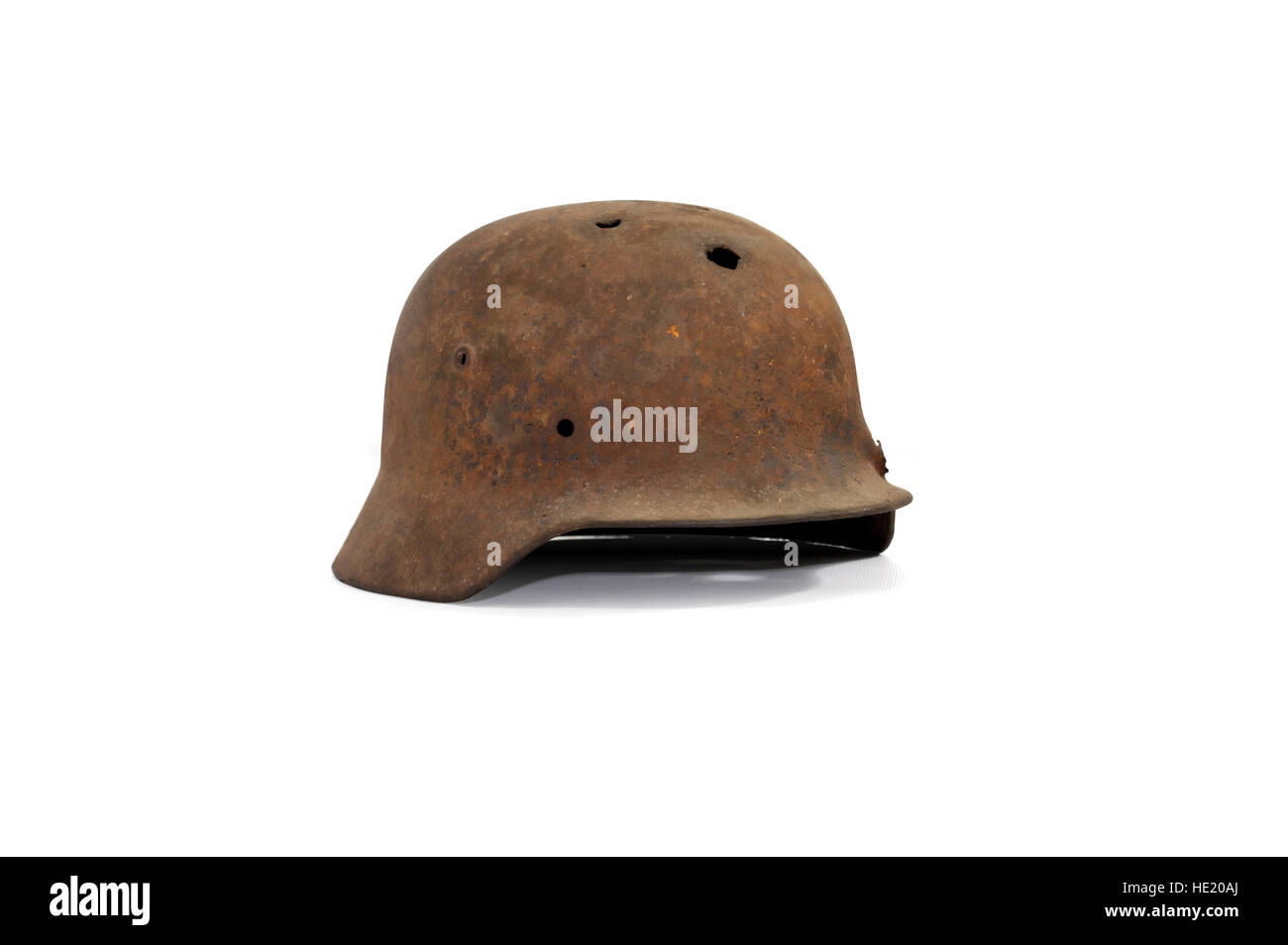 Rusty and holed German military helmet on white background Stock Photo
