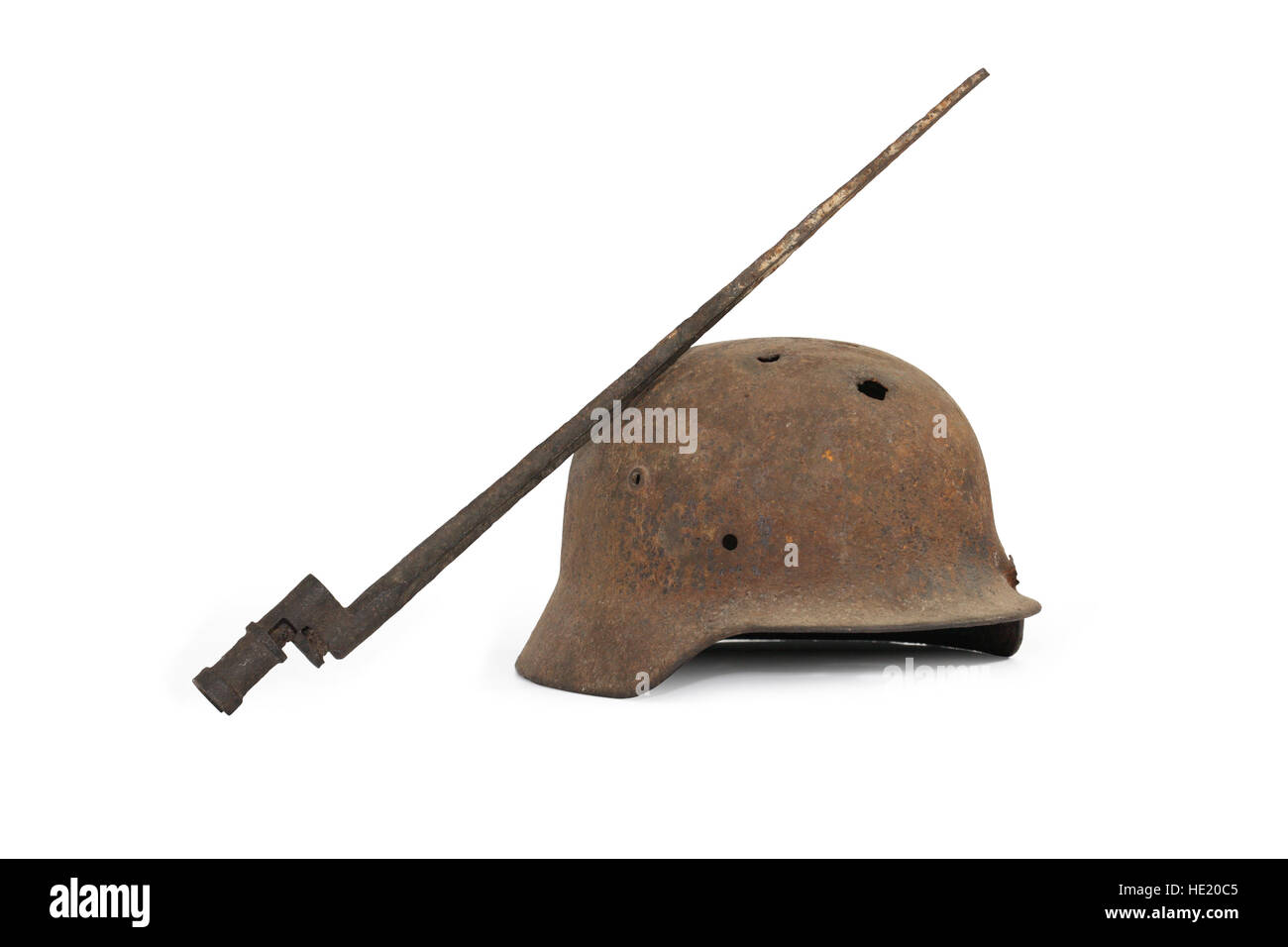 Rusty and holed German military helmet and Russian bayonet on white background Stock Photo