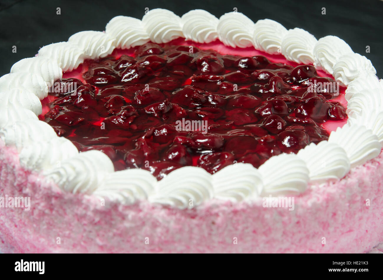 Jelly cake with coconut flakes and cream - Stock Image
