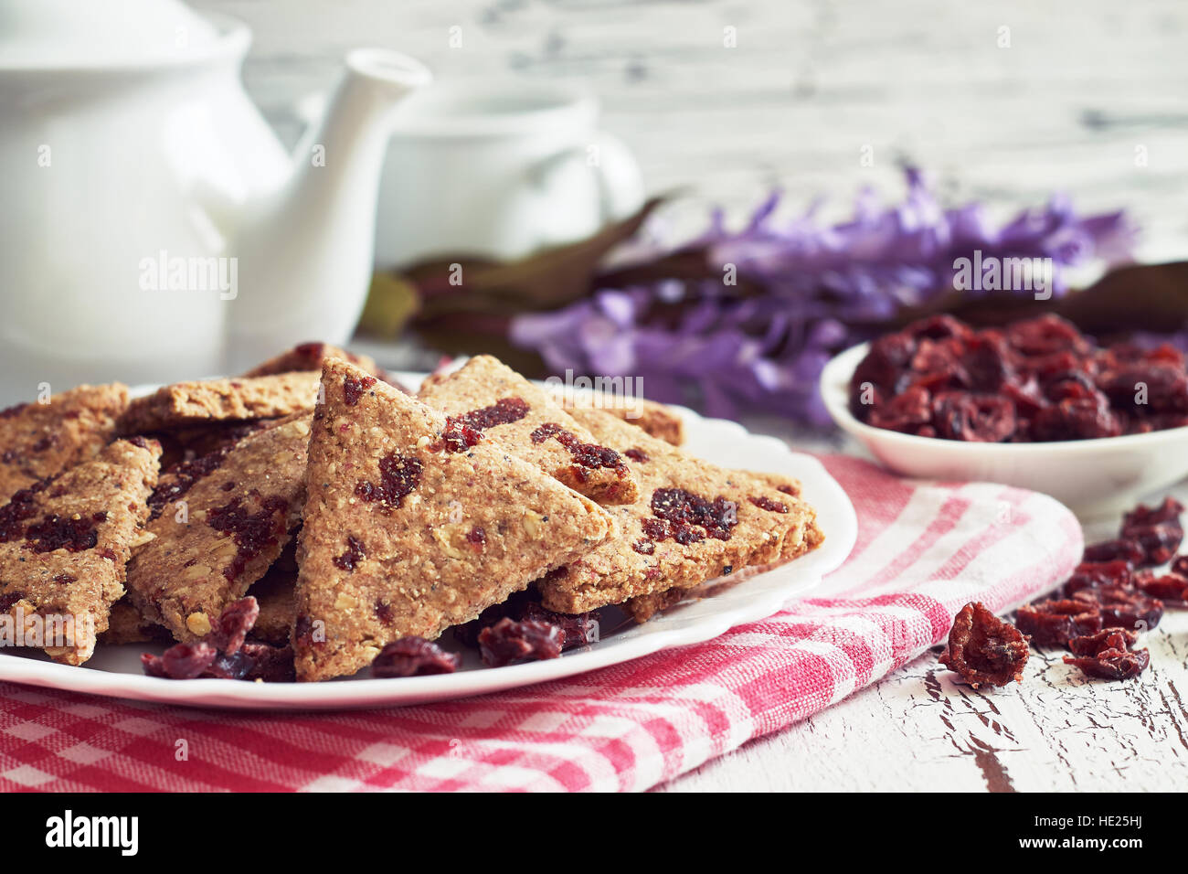 Whole wheat cookies with dried cranberries on white rustic wooden background - Stock Image