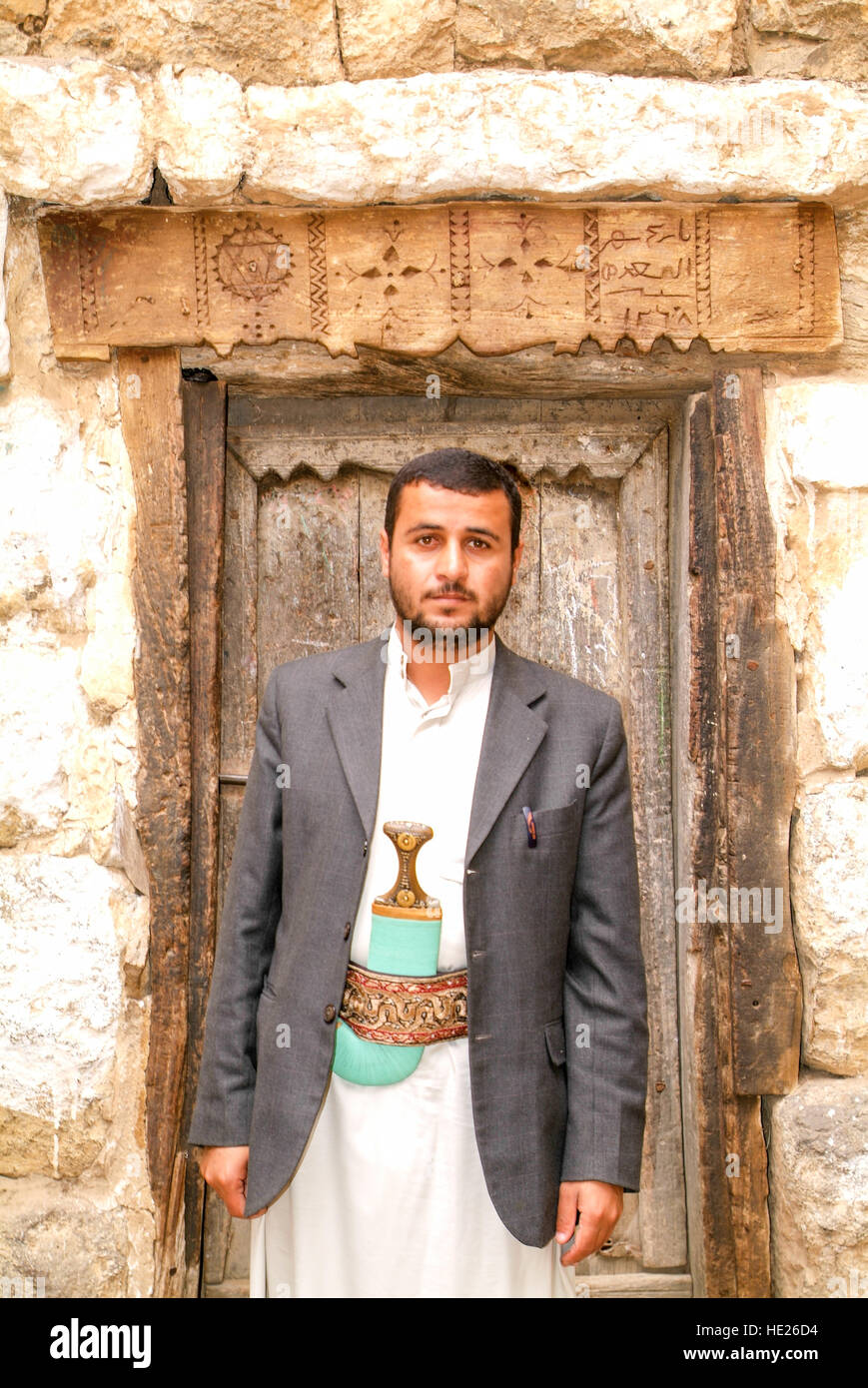 Al Hajjarah, Yemen - 7 january 2016: man posing in front of an old jew door of a house at the village of Al Hajjarah - Stock Image