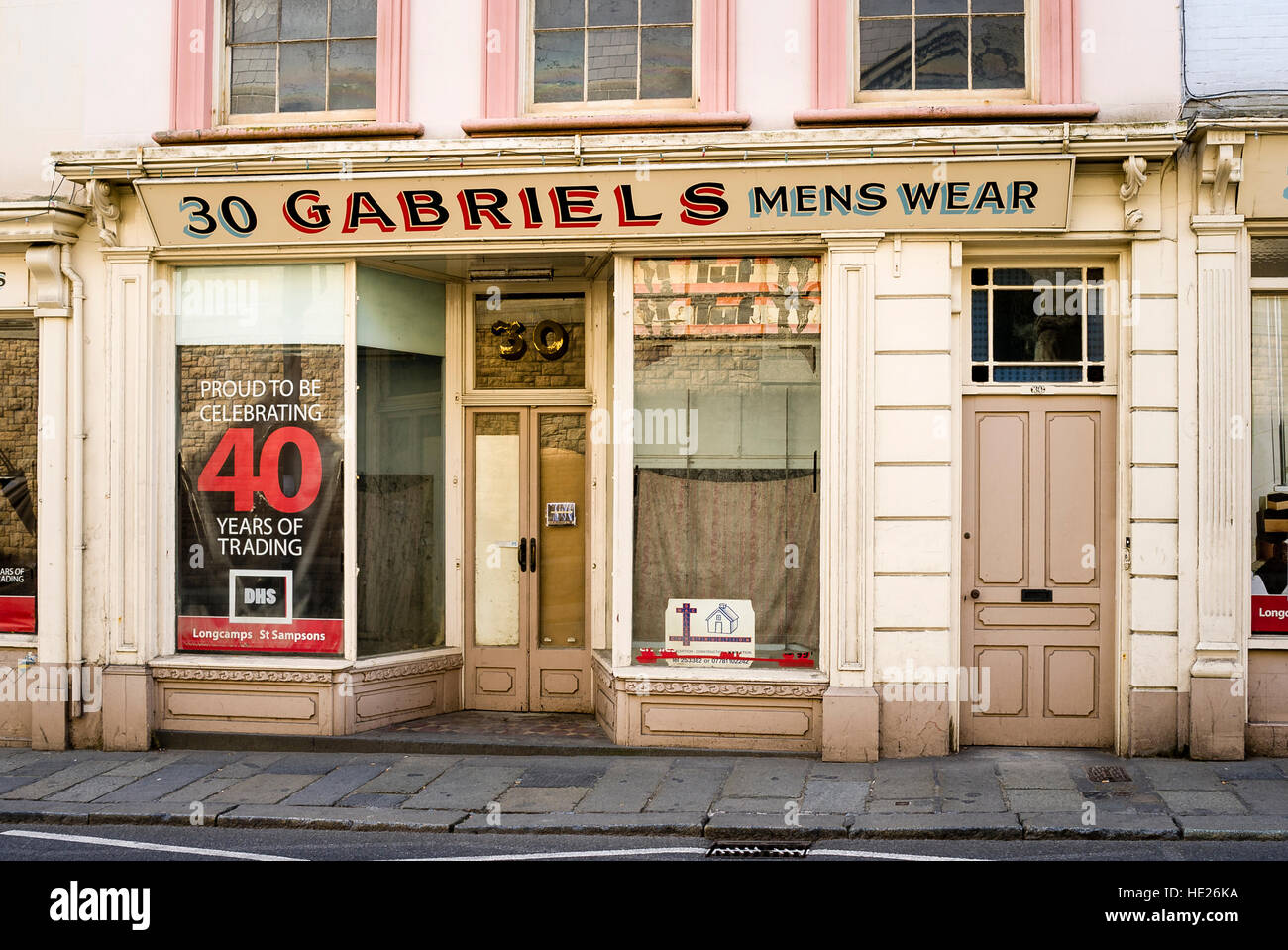 A former mens wear clothing shop in St Peterport UK awaiting its fate or redevelopment - Stock Image