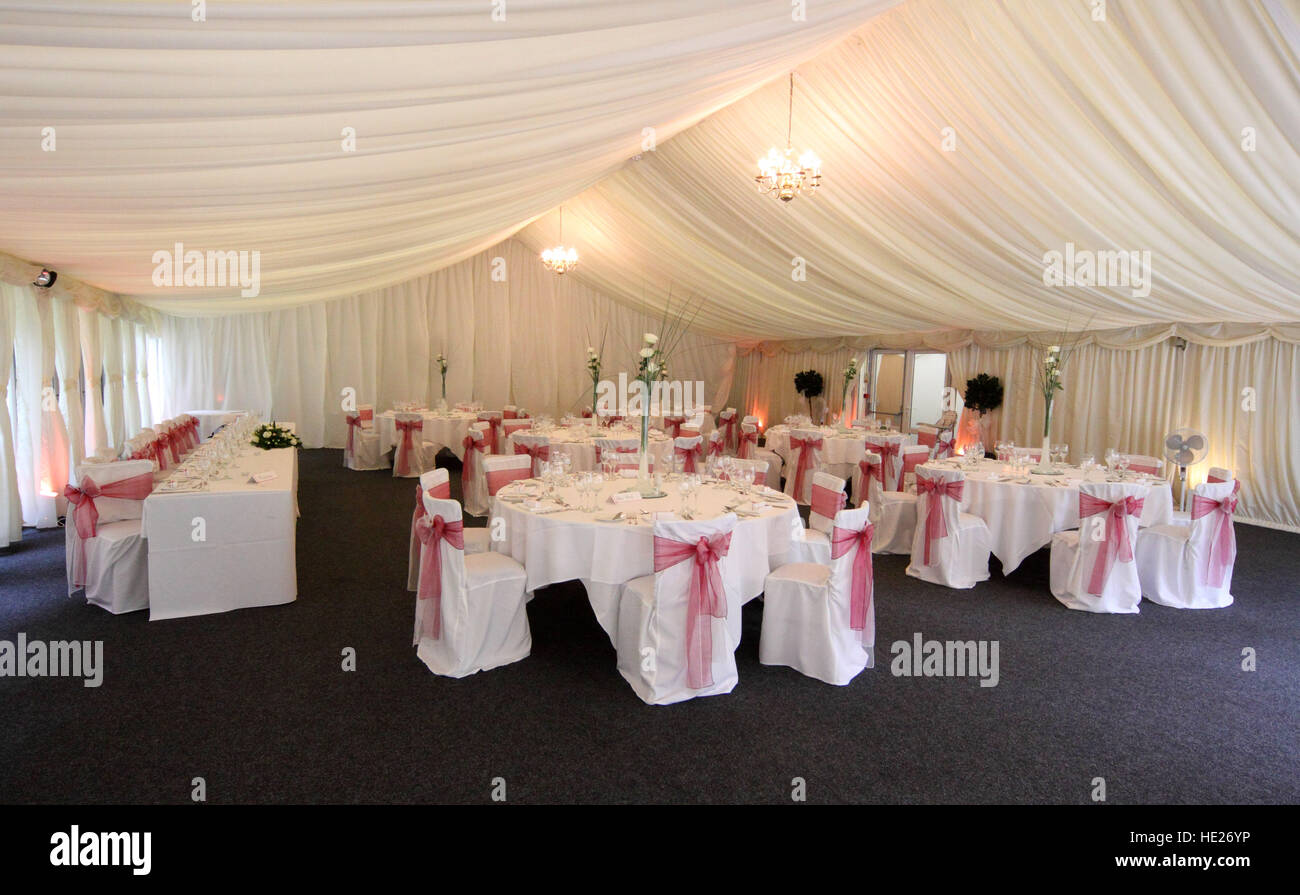 A tented room draped with fabric and laid out for a wedding breakfast, reception meal, and chairs with pink bows. - Stock Image