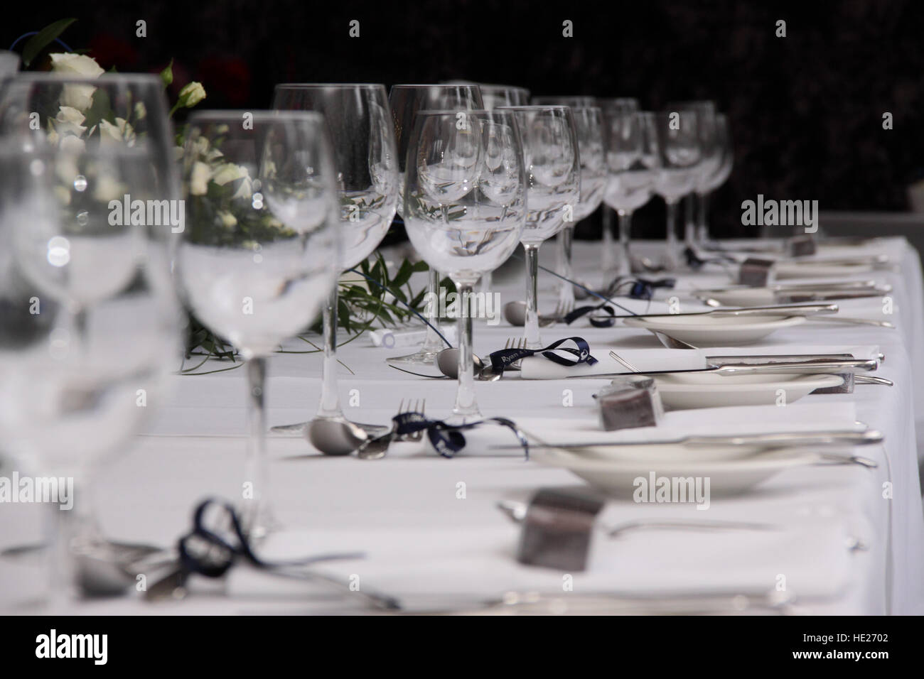 Top table at a wedding reception laid ready with glasses, cutlery and crockery. - Stock Image