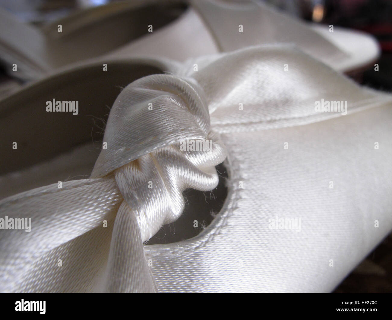White fabric bow tied on a ladies shoe - Stock Image