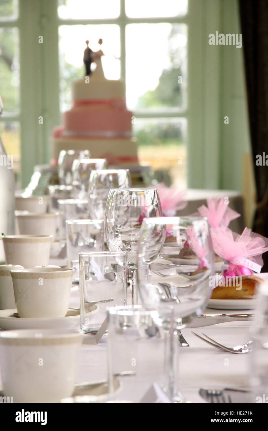 Top table of a wedding reception laid ready, with a wedding cake in the background - Stock Image