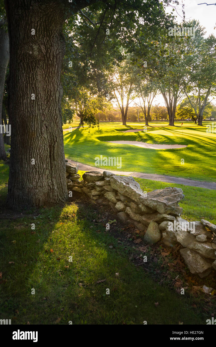 Late afternoon view over a stonewall looking to a golf green and sand trap. - Stock Image