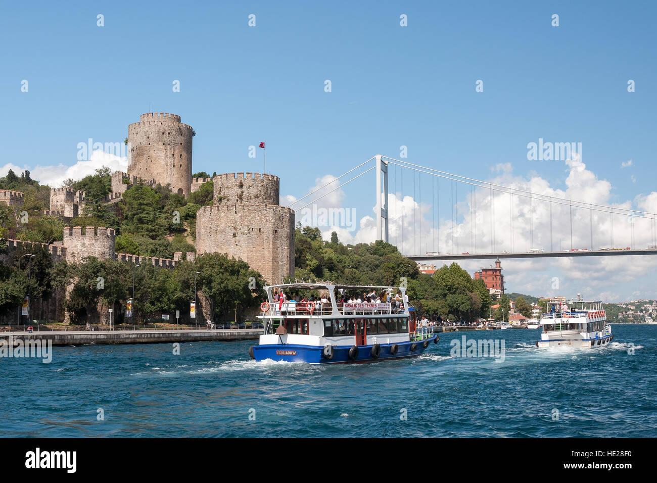 Cruise ships at Bosporus strait with Fatih Sultan Mehmet Bridge and Fortress Rumeli Hisari, Istanbul, Turkey, middle - Stock Image