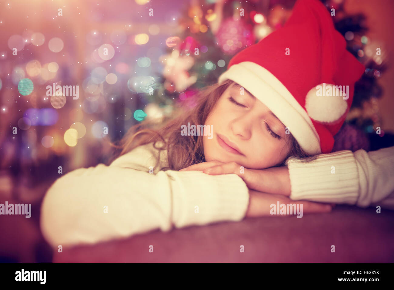 Portrait of a beautiful teen girl wearing red Santa hat sleeping near Christmas tree in anticipation of a gifts - Stock Image
