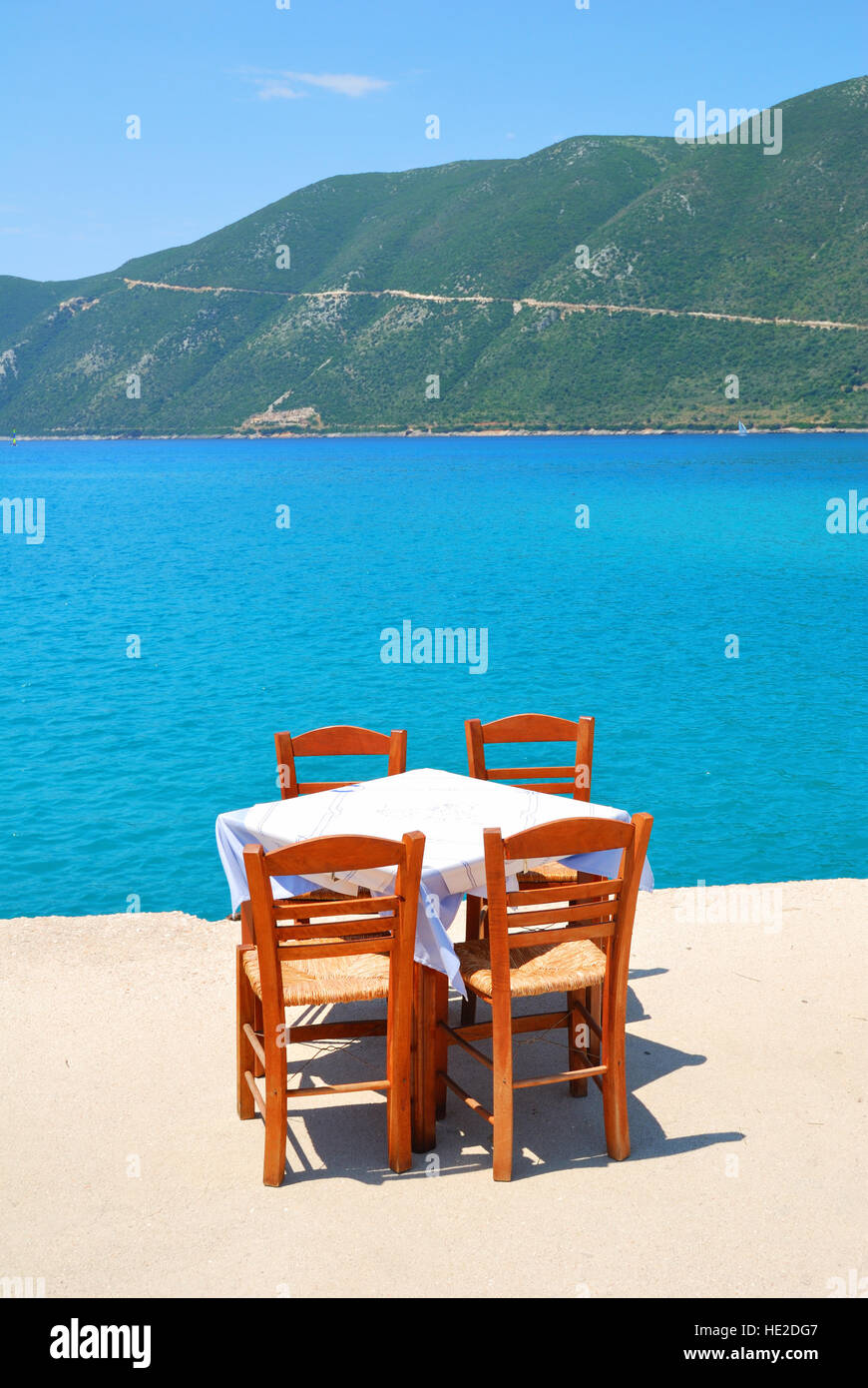 Dining table with chairs in a greek taverna with blue sea and green hills Stock Photo