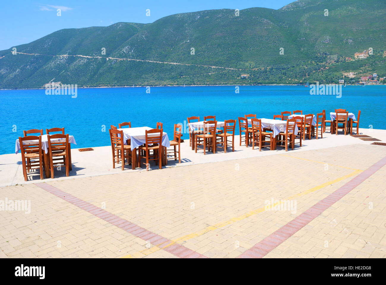Dining tables with chairs in a greek harbour taverna with blue sea and green hills Stock Photo