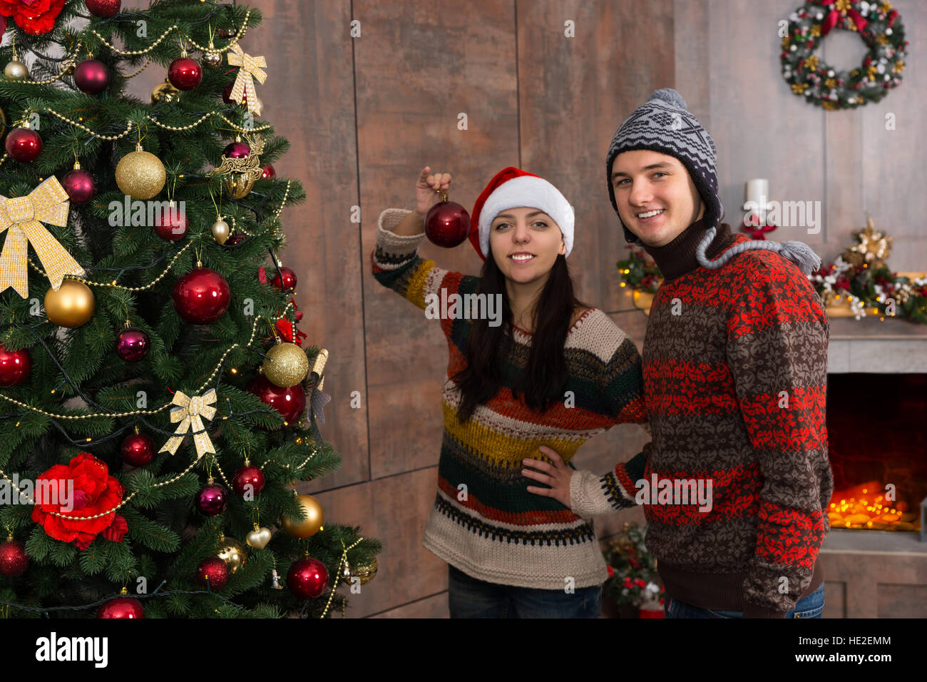 Young Smiling Couple Wearing Funny Hats Decorating For Christmas Hanging The Decorations And Ornaments On Large Tree In Their Living Ro