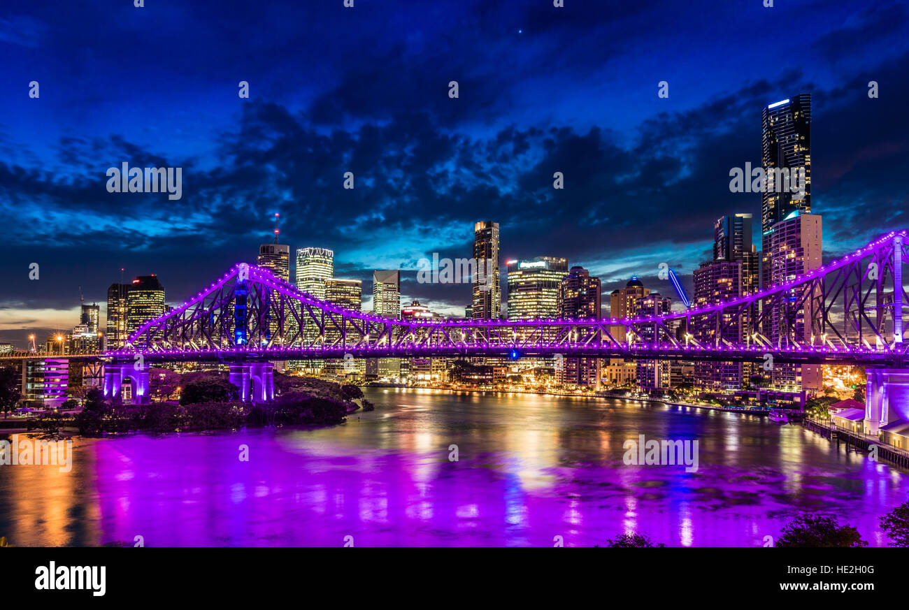 Vibrant night time panorama of Brisbane city with purple lights on Story Bridge, Australia - Stock Image