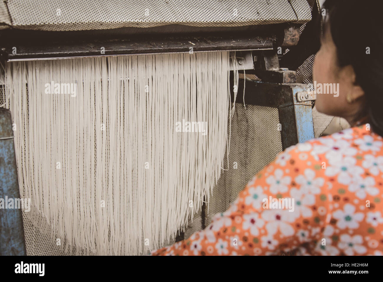 Vietnamese lady making rice noodles along the Mekong River - Stock Image