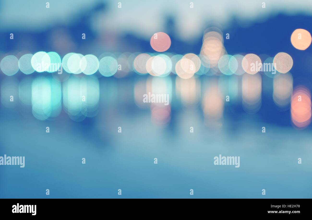 Abstract multicolor blurred bokeh light with water reflection on blue background - Stock Image