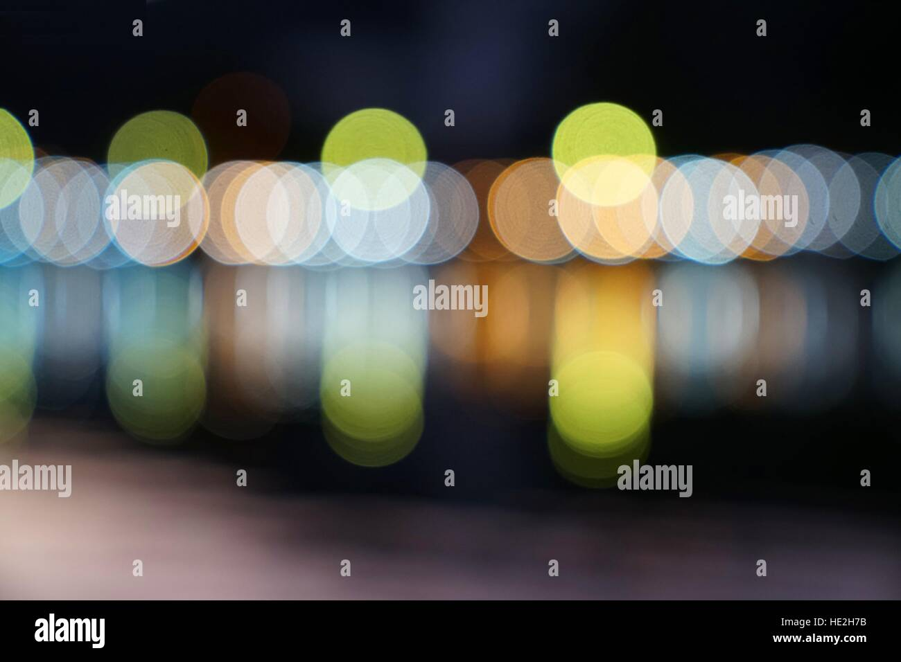 Abstract multicolor blurred bokeh light with water reflection at night - Stock Image