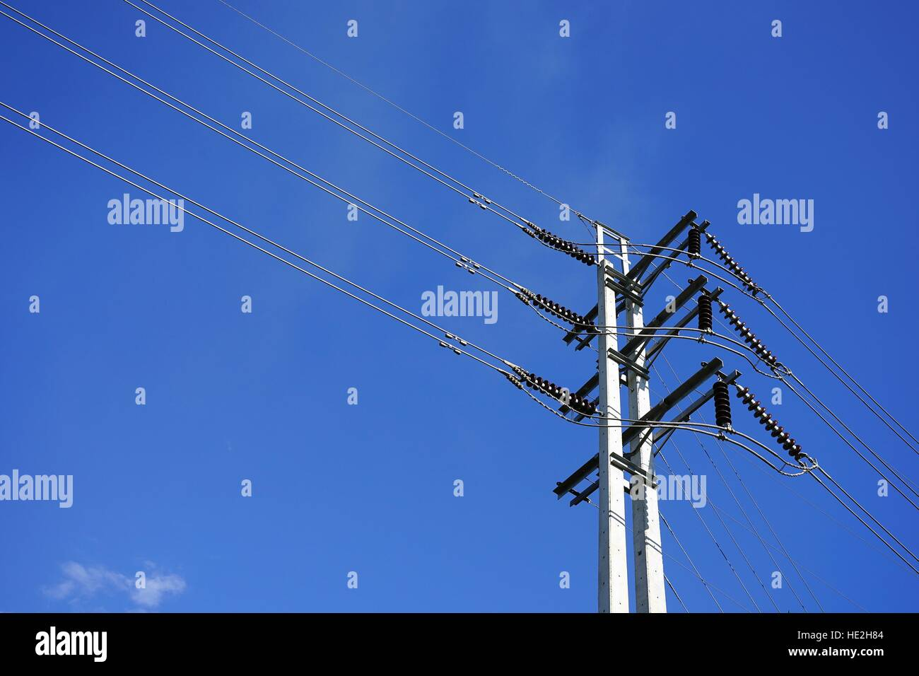 High voltage electric post with power line cables against blue sky - Stock Image