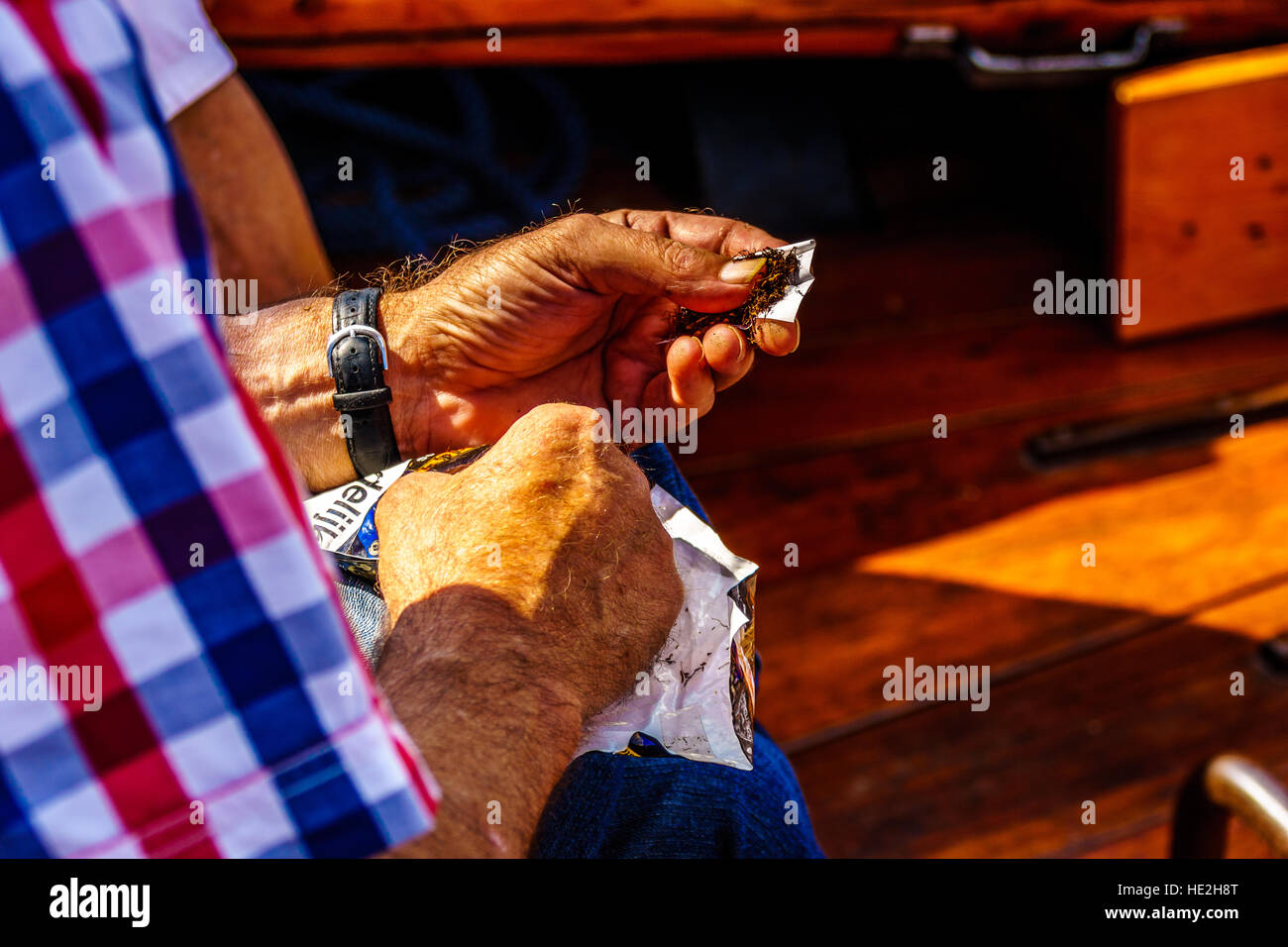 Sailor Rolling a Cigarette on during a Bot Ride on a wooden Botter Boat on the Veluwemeer in the Netherlands - Stock Image