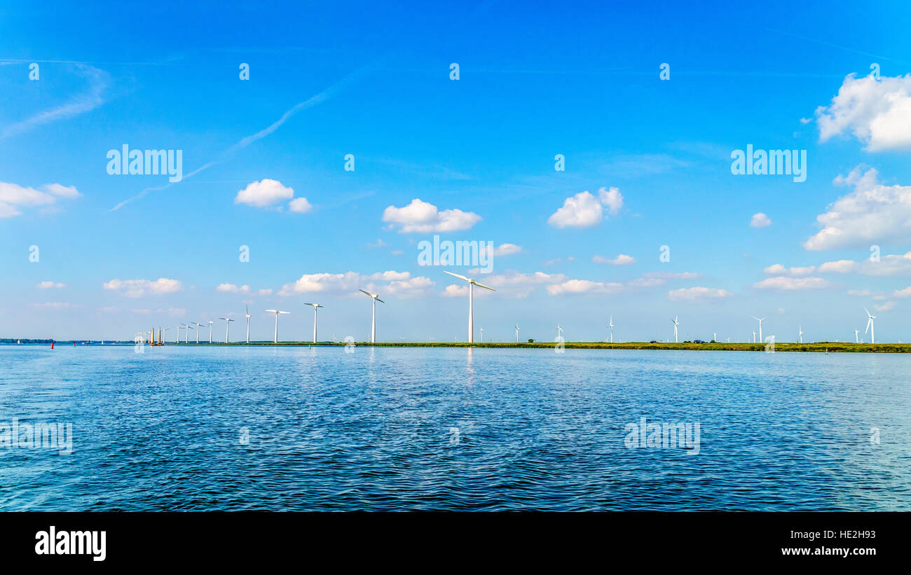 Wind Farm with Two and Three bladed Wind Turbines along the Shore of Veluwemeer in the Netherlands - Stock Image