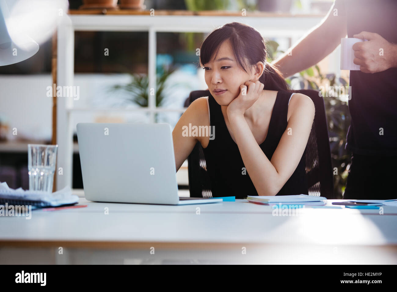 Shot of asian young woman sitting at her desk working on laptop with male colleague standing by. - Stock Image
