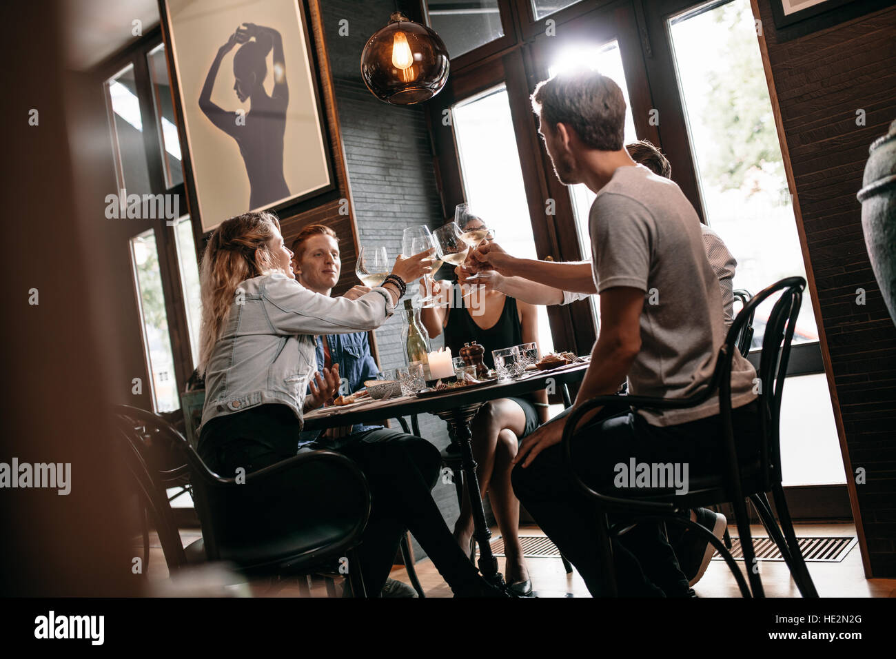 Group of friends toasting wine at restaurant. Young man and woman sitting at table and toasting drinks at cafe. - Stock Image