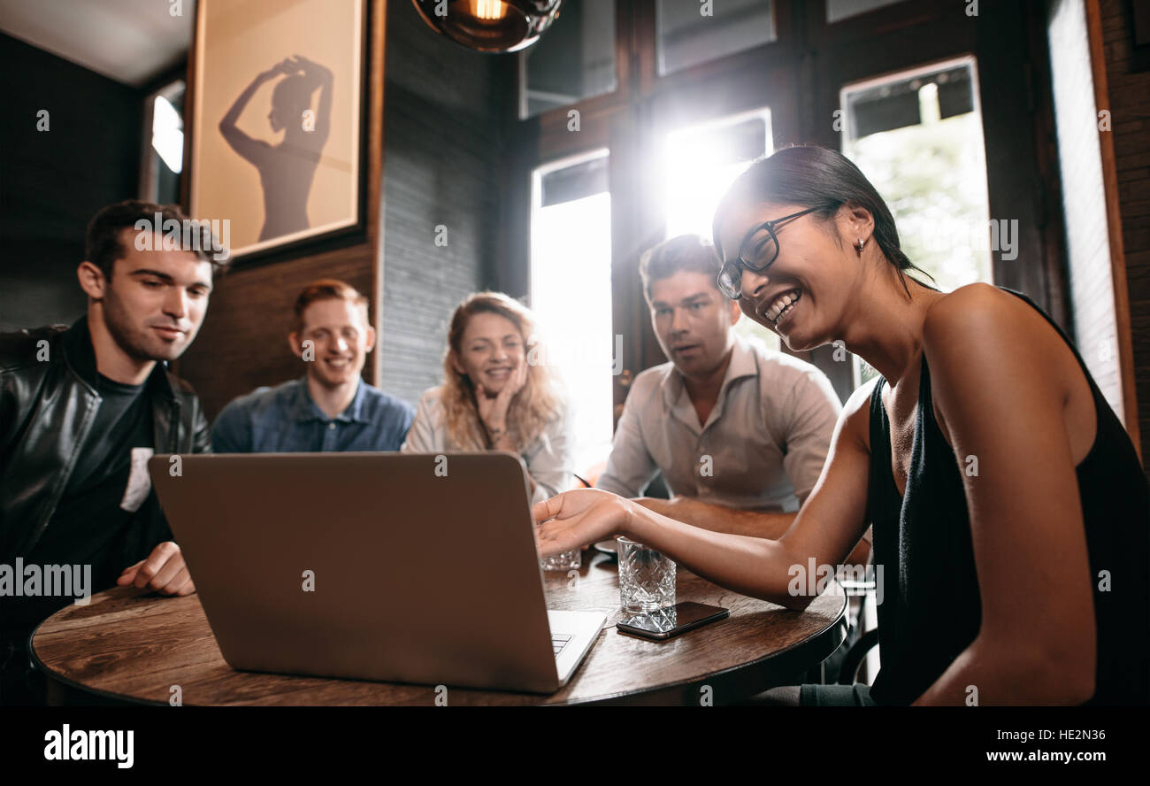 Smiling young woman showing something on laptop to her friends. Group of young men and women at cafe looking at - Stock Image