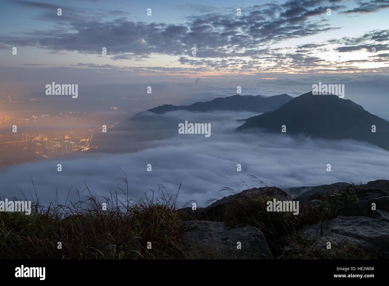 Clouds rolling over mountain peaks on Lantau Island, viewed from Lantau Peak (the 2nd highest peak in Hong Kong, - Stock Image
