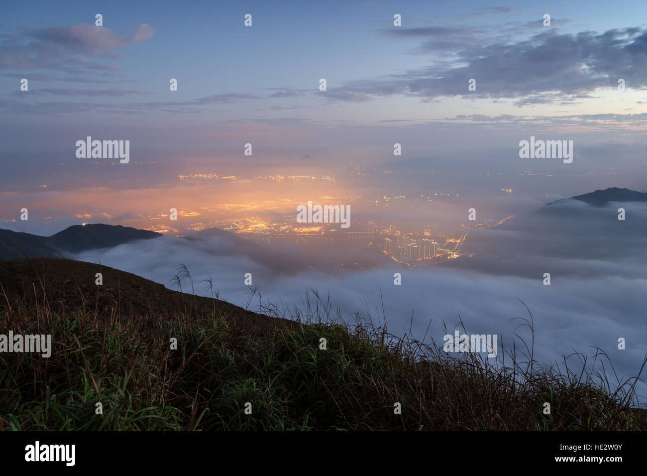 Lights of Tung Chung New Town below clouds on Lantau Island, viewed from the Lantau Peak on Lantau Island in Hong - Stock Image