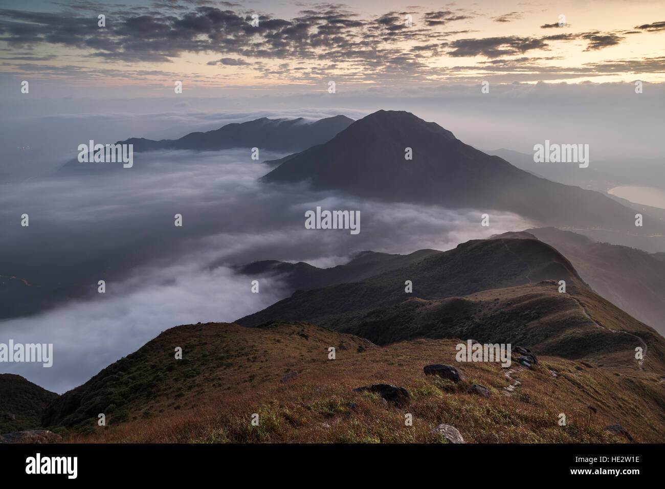Clouds rolling over a mountain on Lantau Island, viewed from the Lantau Peak (the 2nd highest peak in Hong Kong, - Stock Image