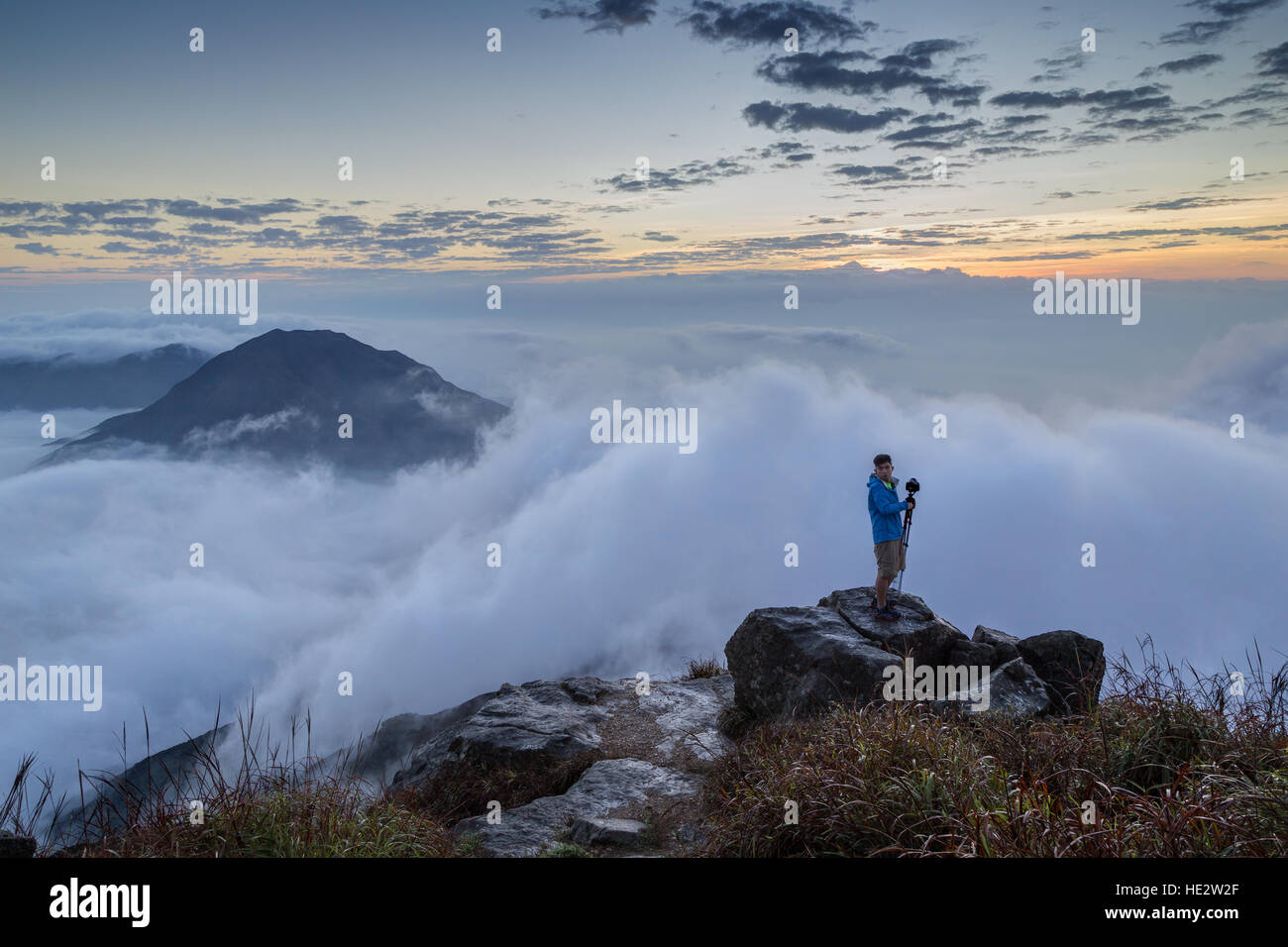 View of clouds and a man with a camera and tripod standing on a rock at the Lantau Peak on Lantau Island in Hong - Stock Image