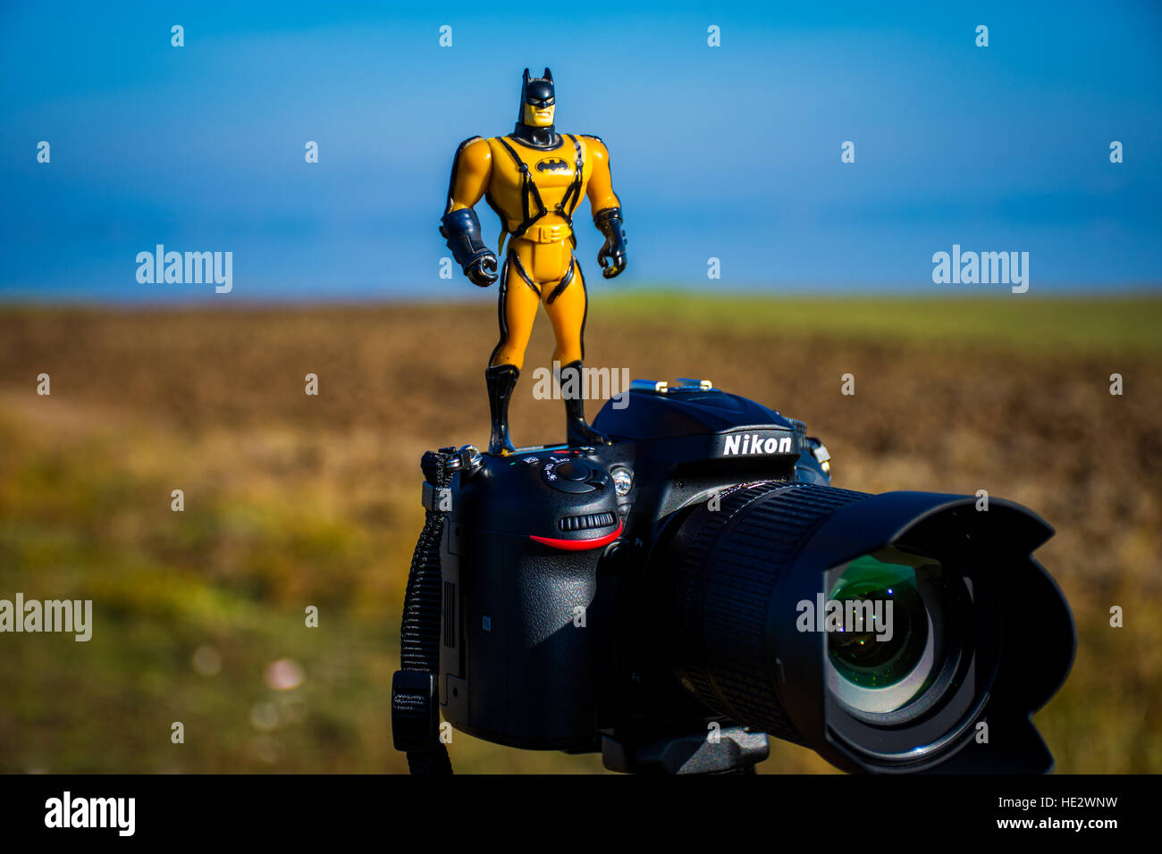 Batman in a yellow suit standing on a Nikon DSLR Camera - Stock Image