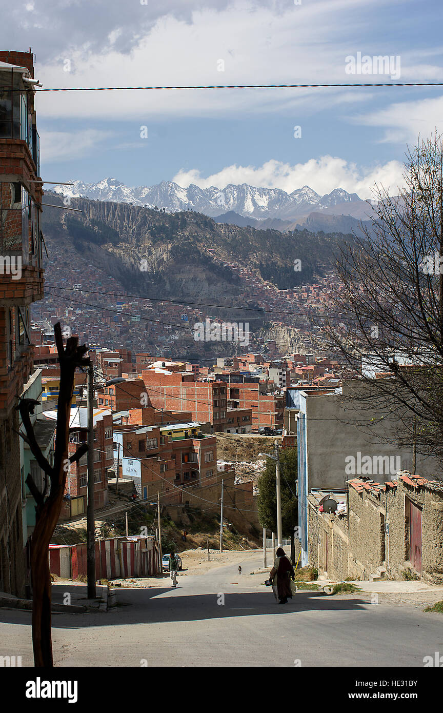 A silhoueete of a woman on the streets of La Paz, Bolivia, Illimani and snowy white mountain peaks of the Cordillera - Stock Image
