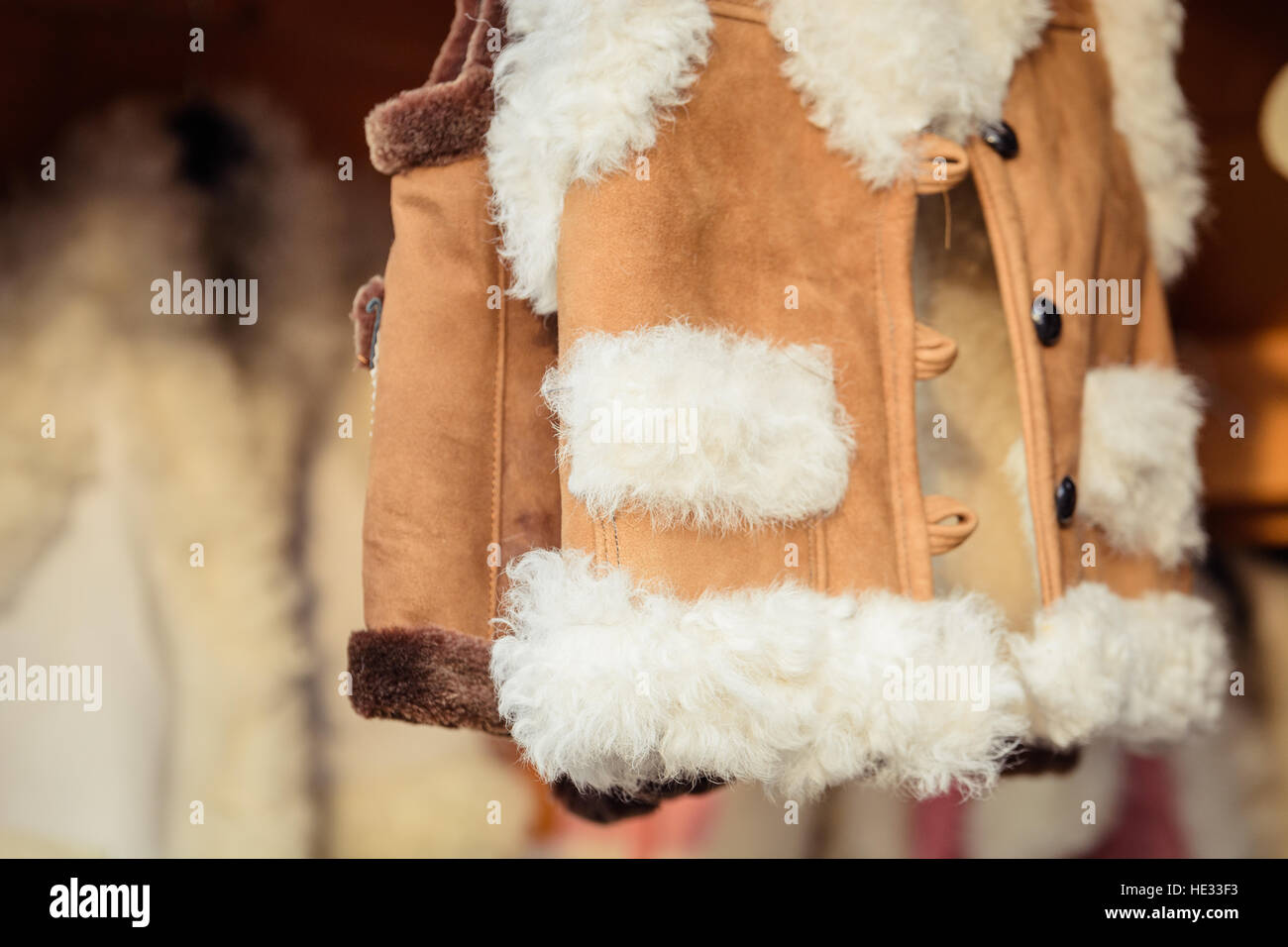 Traditional sheepskin and wool clothing. Vest made by hand from genuine leather and fleece. - Stock Image