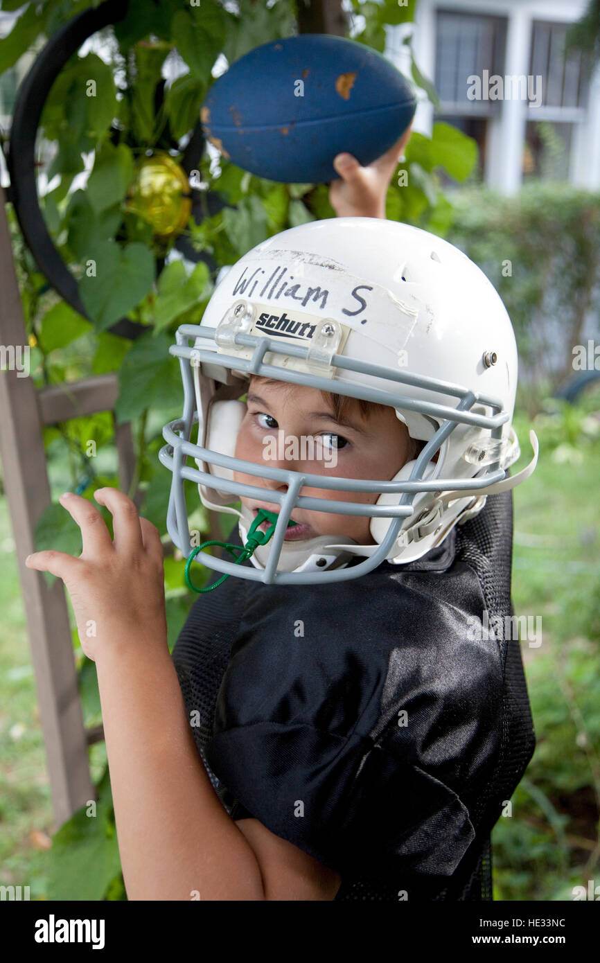 Boy age 10 practices passing football while wearing helmet with face guard. St Paul Minnesota MN USA - Stock Image