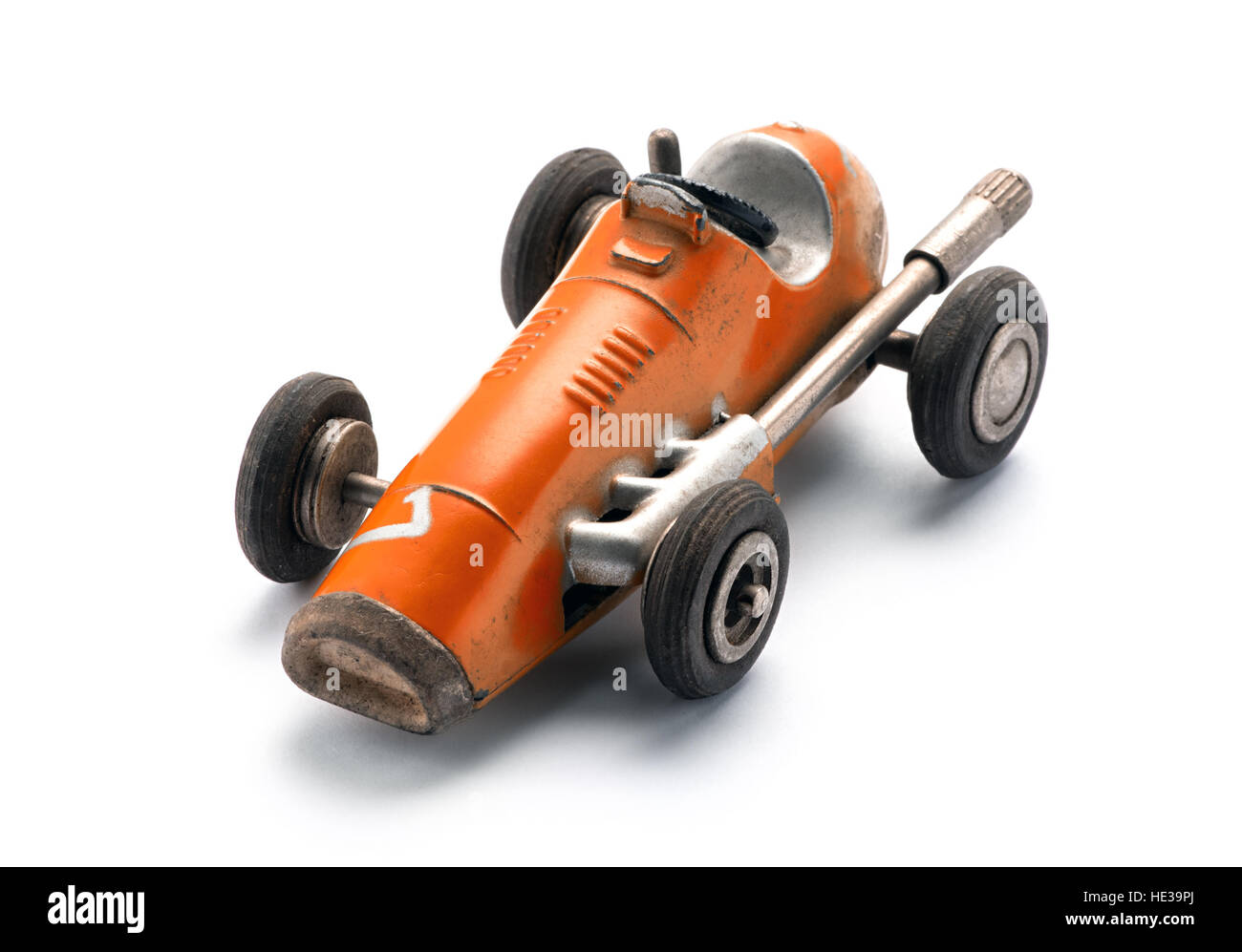 Colorful orange vintage toy racing car in a three quarter front view from above on a white background with copy - Stock Image