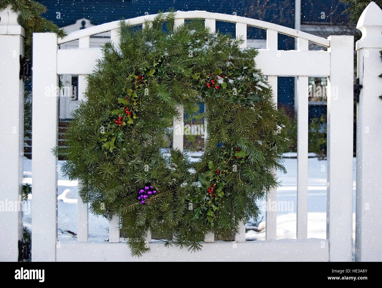 pine wreath with christmas decorations on white fence gate