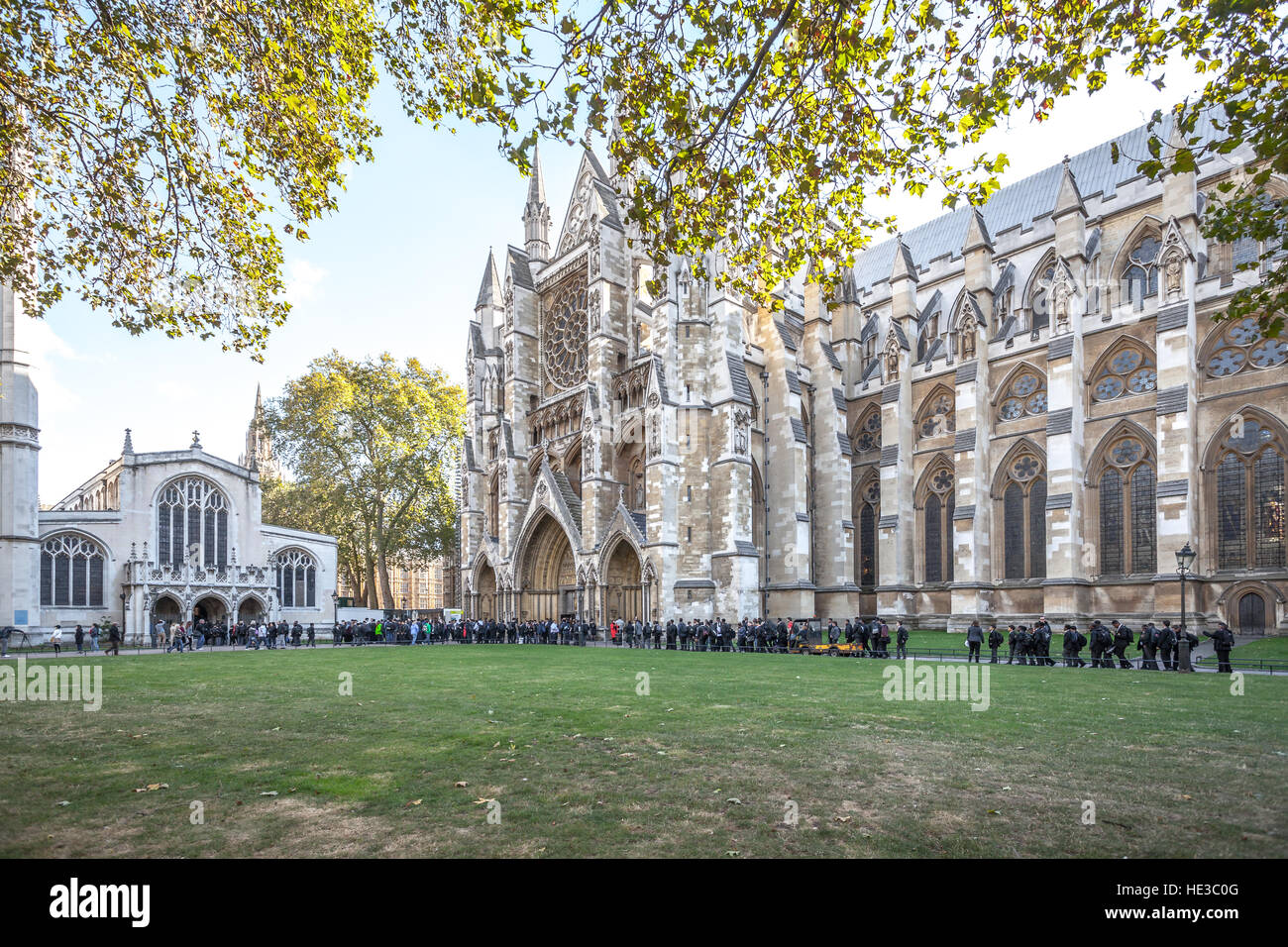 London UK, groups of schoolchildren waiting in line to enter on Westminster Abbey - Stock Image
